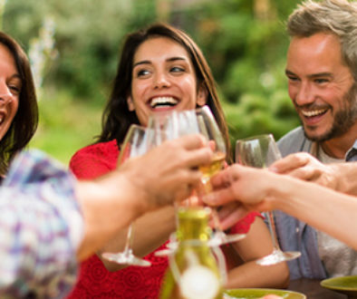 Group of friends toasting during a party on a terrace in summer